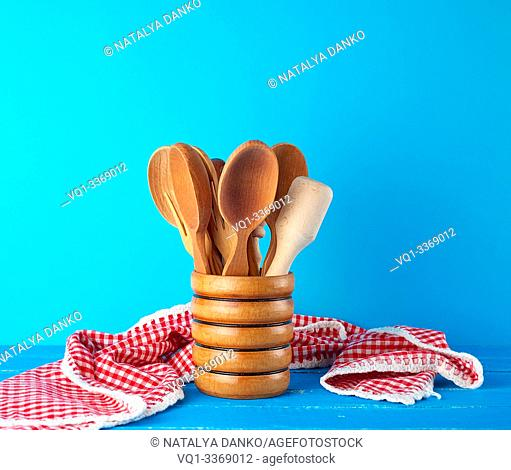 wooden spoons in a wooden container on a blue table, kitchen backdrop