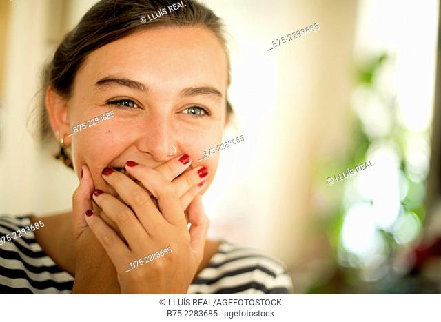 Portrait of young woman covering her mouth with hand, smiling, happy and joy