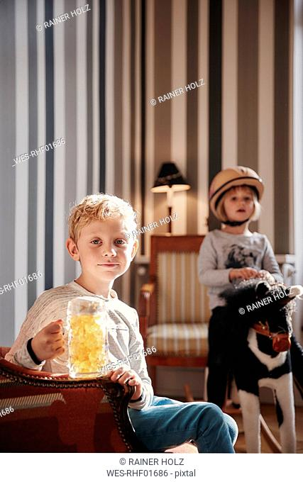 Boy holding fruit gum beer mug and sister on rocking horse