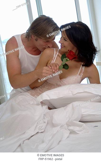 Couple in bed, woman is holding a rose