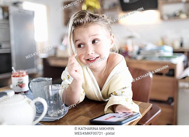 Portrait of smiling little girl with smartphone in the kitchen