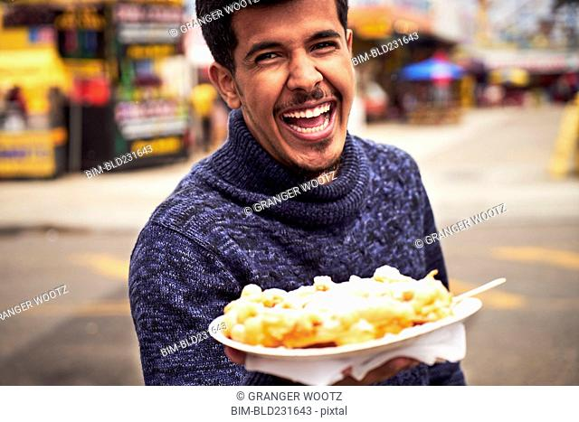 Laughing man showing plate of food at amusement park