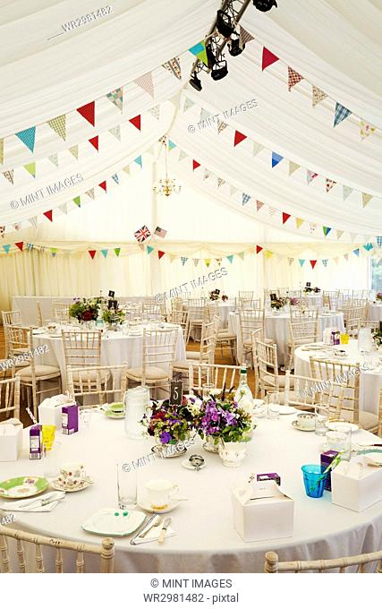 Interior view of a wedding marquee with set tables and decorated with bunting