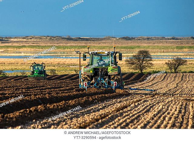 Tractors carrying out deep bed shaping followed by sowing the fields in early springs time at Burnham Overy in North Norfolk, East Anglia, England, UK