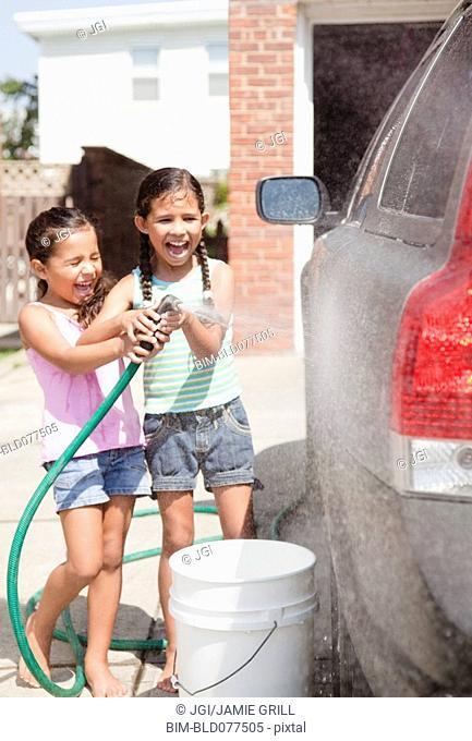 Hispanic girls washing car