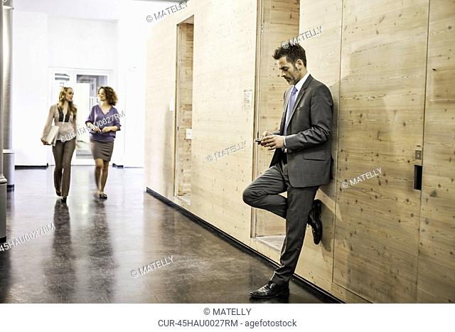 Businessman using cell phone in hallway