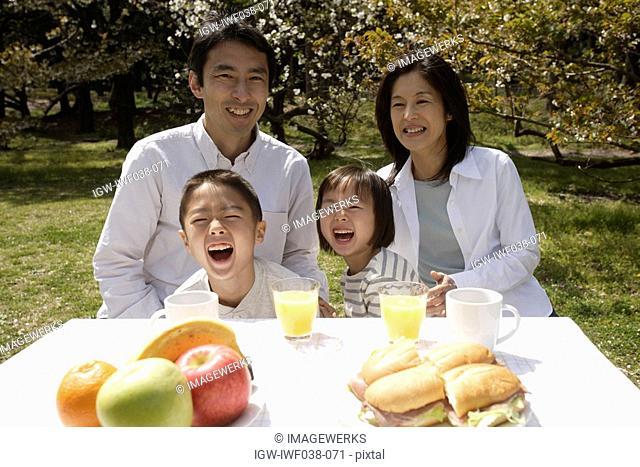 Portrait of a family smiling in garden by breakfast table