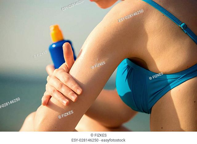 Young woman in blue swimwear on the beach holding bottle of suntan lotion, applying sun cream on her arm before tanning, close up