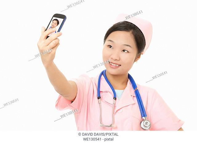 Beautiful Chinese nurse using a cell photo to take a Selfie of herself