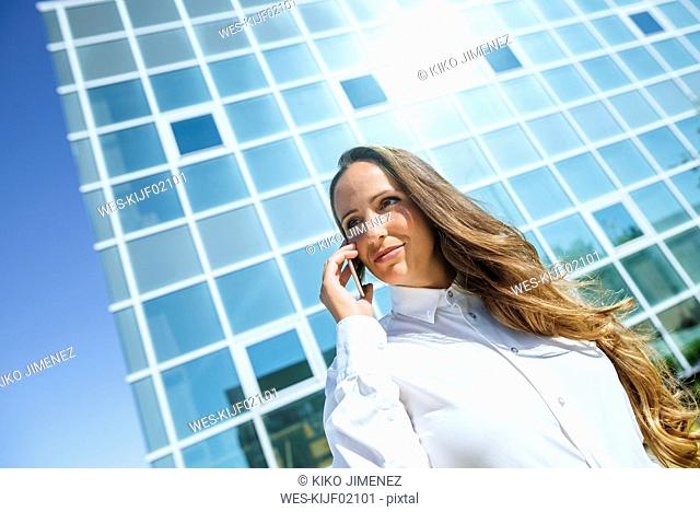 Smiling businesswoman on cell phone outside office building