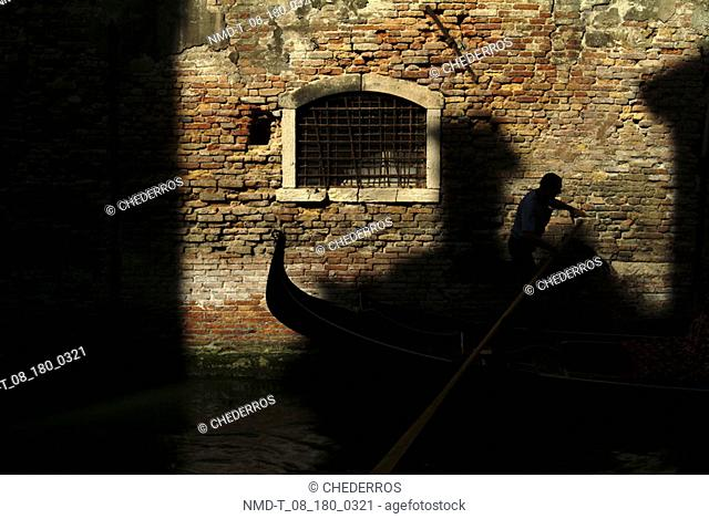 Gondolier punting a gondola in a canal, Venice, Veneto, Italy