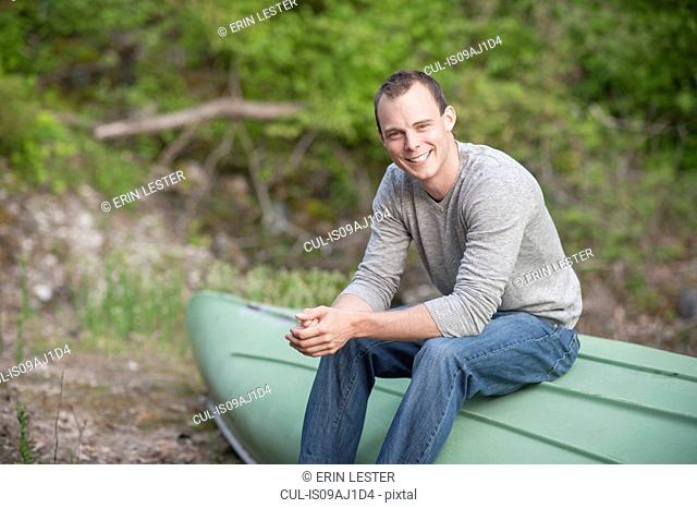 Portrait of young man sitting on upturned boat