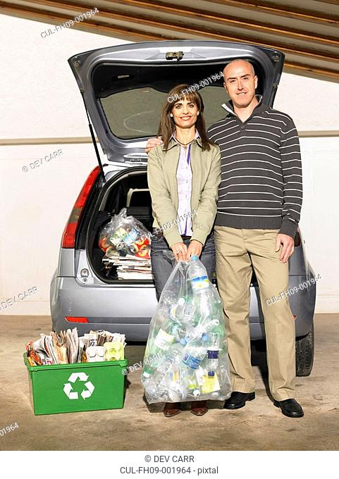 Couple standing by car holding recycling, portrait
