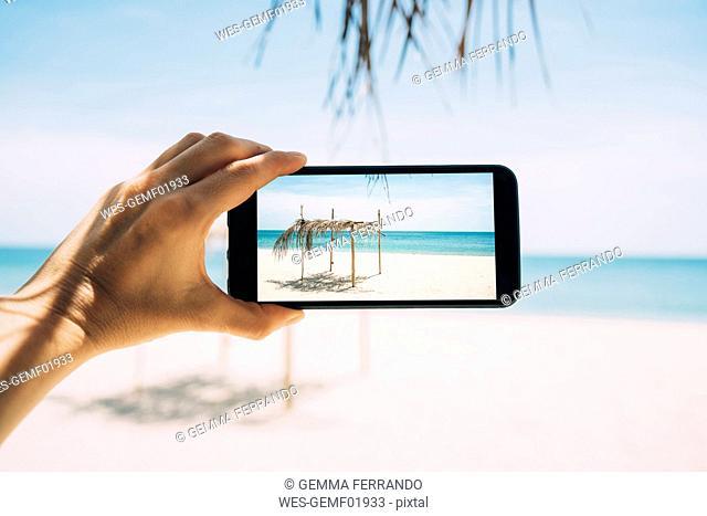 Thailand, Koh Lanta, Virgin Paradise Beach, woman taking photo with cell phone