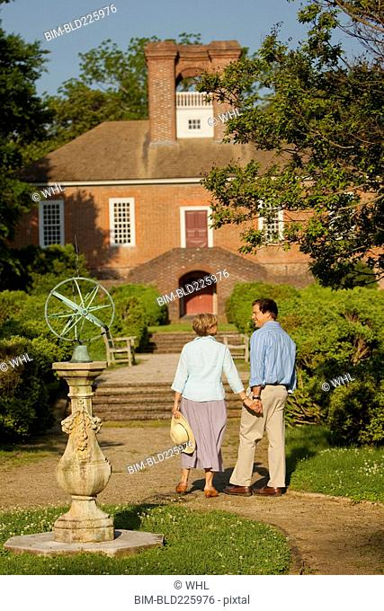 Couple holding hands in garden near house
