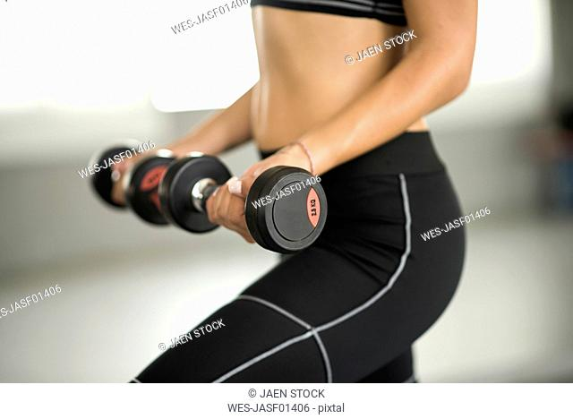 Close-up of woman training biceps in gym