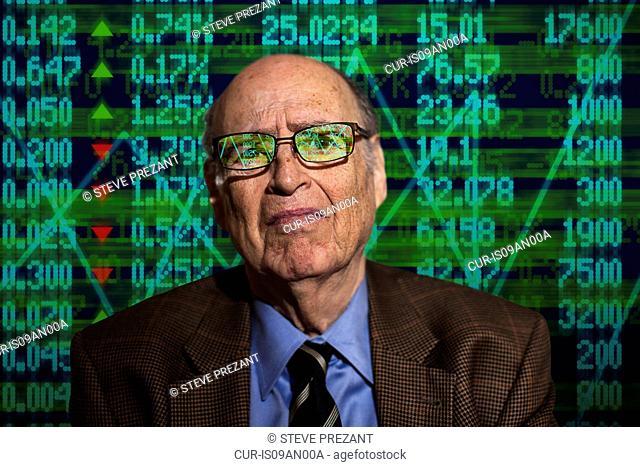 Portrait of worried senior businessman in front of financial digital display
