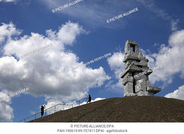 17 June 2019, North Rhine-Westphalia, Gelsenkirchen: Clouds are dragging over the sculpture Himmelstappe on the Rheinelbe slagheap