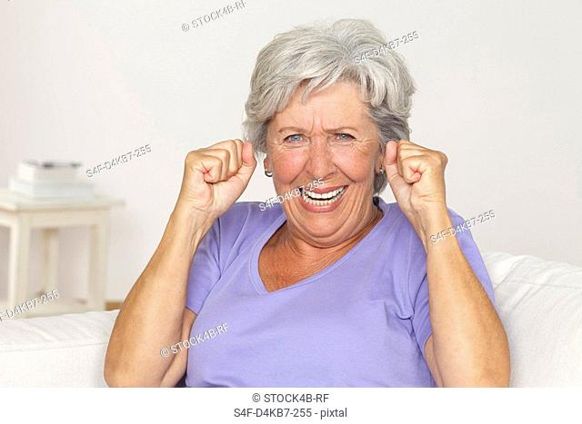 Senior woman cheering with clenched fists