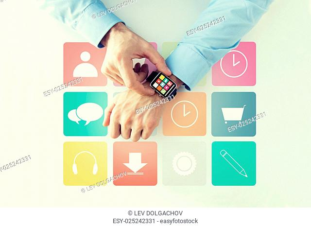 business, technology and people concept - close up of male hands setting smart watch with application icons on screen