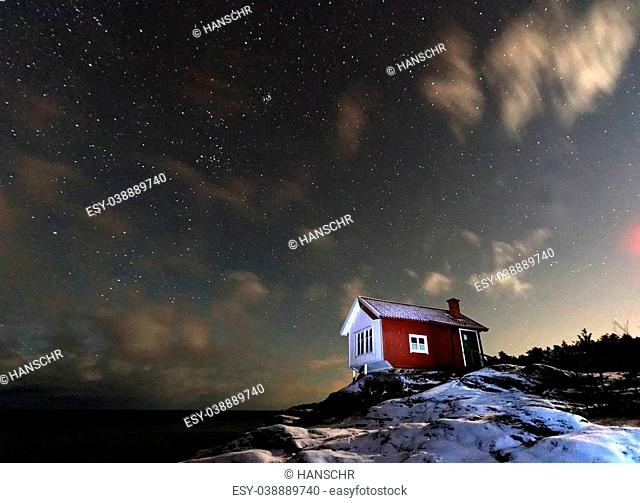 Starry and cloudy sky above a red and white cottage in the swedish archipelago