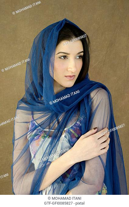 Beautiful Woman covered with blue scarf looking away