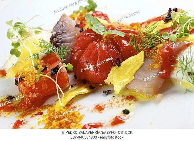 Tomato salad with fish and gold leaf