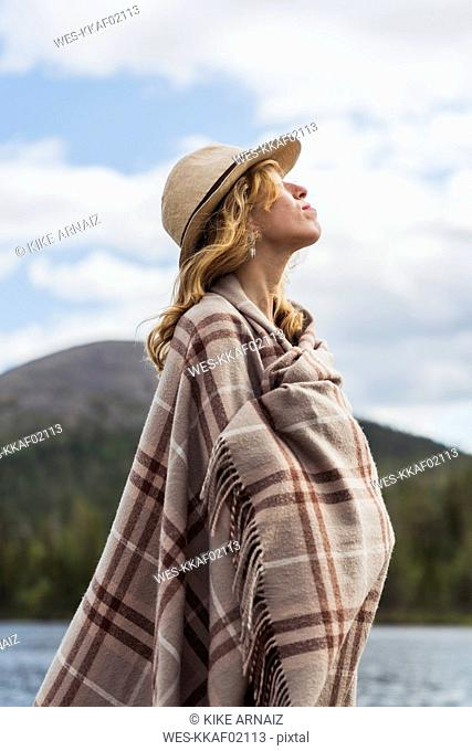 Finland, Lapland, woman wearing a hat wrapped in a blanket standing at the lakeside