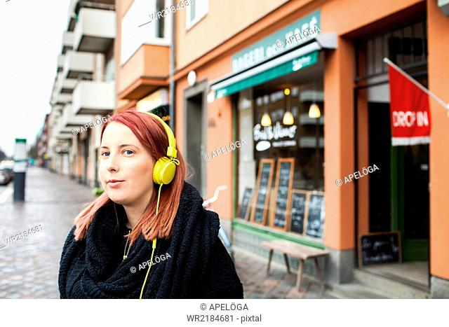 Young woman listening music through headphones outside cafeteria