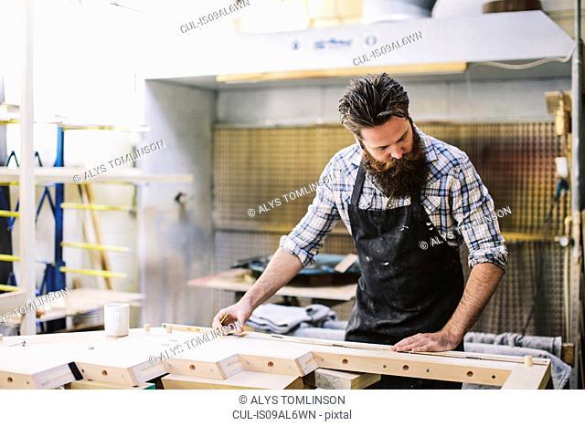 Cropped shot of mid adult craftsman measuring wood in organ workshop