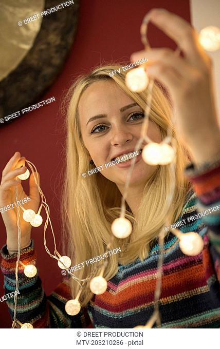 Young woman looking at fairy lights in the living room, Bavaria, Germany