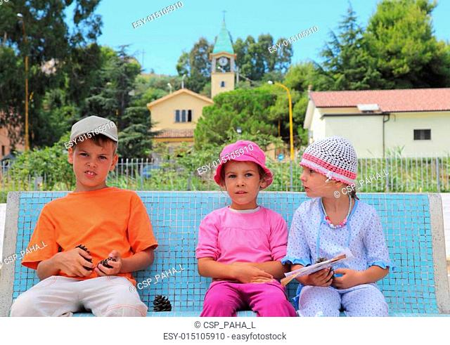 little brother and two sisters are sitting on blue bench. boy holding cone. in background of Italian church