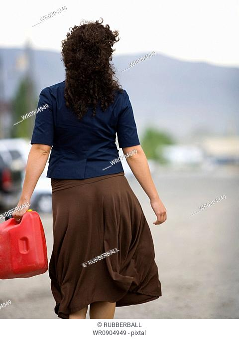 Rear view of a young woman holding a gas can and walking
