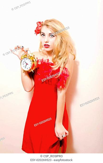 cfc8e8536 holding alarm-clock beautiful glamour young blond pinup woman in red dress  with flower in