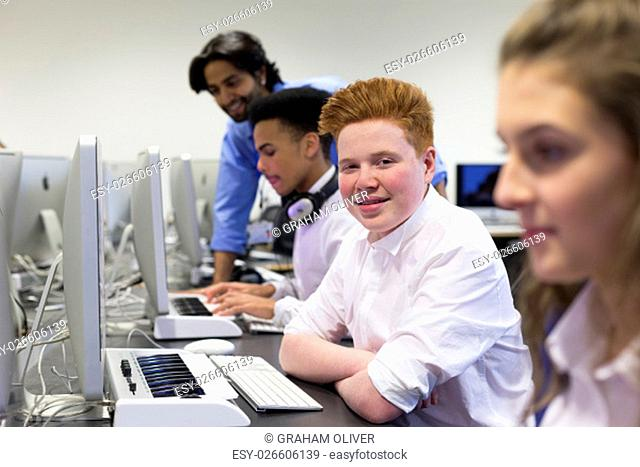 Students using computers in a school lesson. One student is smiling at the camera. There is a teacher helping another student in the background