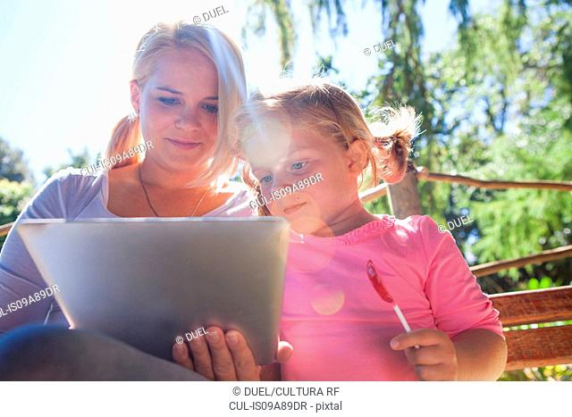 Mother using laptop, girl with lollipop