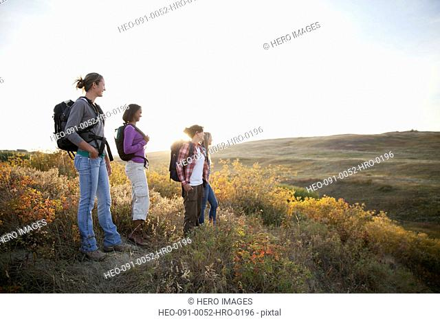 Friends with backpacks standing on grassy hill