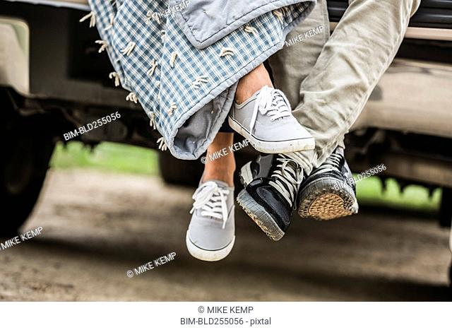 Feet of couple wrapped in blanket sitting on bed of pick-up truck