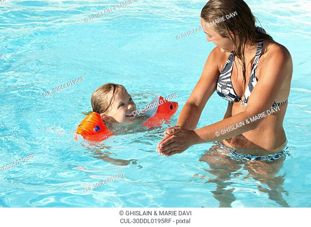 Mother and son playing in swimming pool