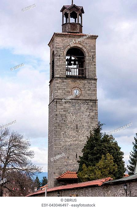 old bell tower with a clock on the background of blue sky