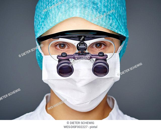Portrait of young doctor wearing mask and magnifying spectacles