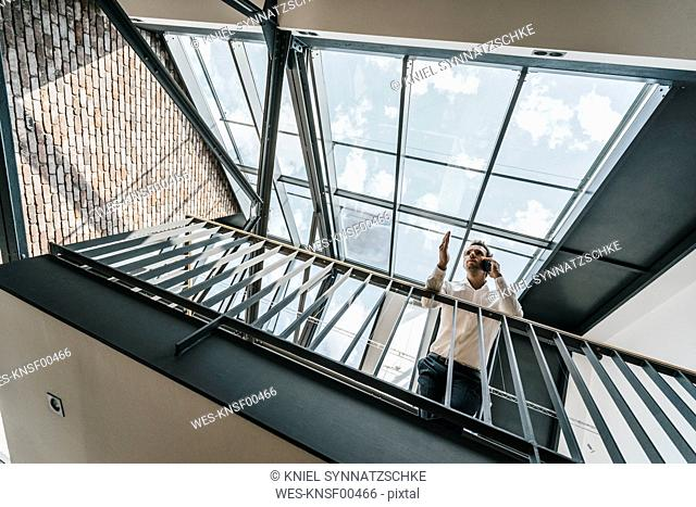 Businessman on upper floor in office talking on cell phone
