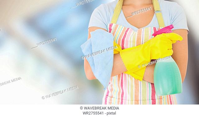 Woman in apron with cleaner against blurry window