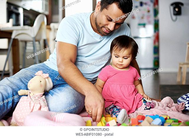 Father and baby girl playing with building blocks at home