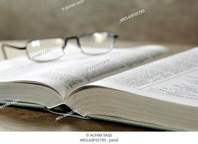 Eyeglasses on opened book, close-up