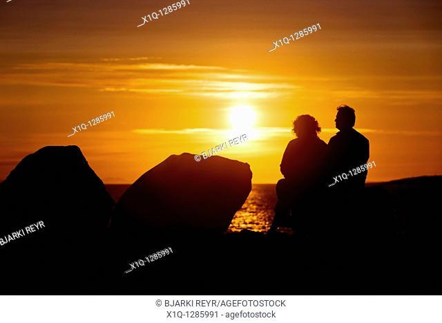 People sitting and enjoying the midnight sun setting over the Atlantic Ocean  Reykjavik Iceland