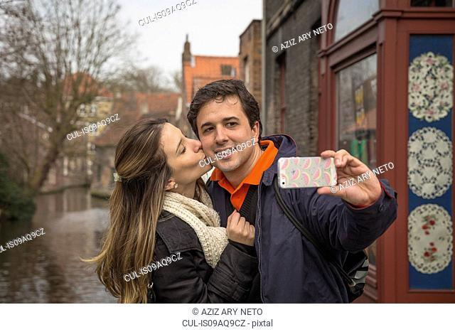 Couple taking selfie on smartphone, Bruges, Flanders, Belgium