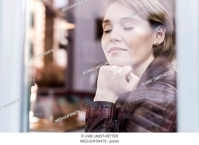 Young woman with closed eyes behind windowpane