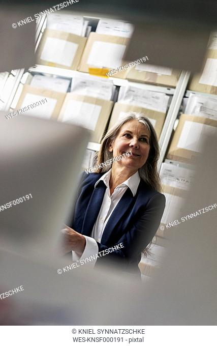 Smiling senior businessswoman in storeroom