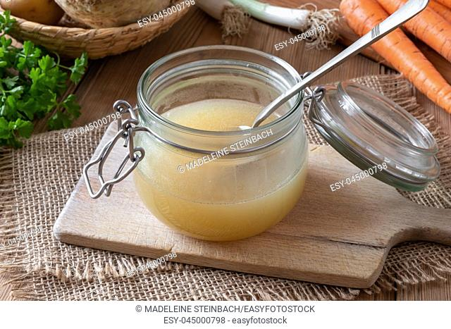 Chicken bone broth in a glass jar, with fresh vegetables in the background